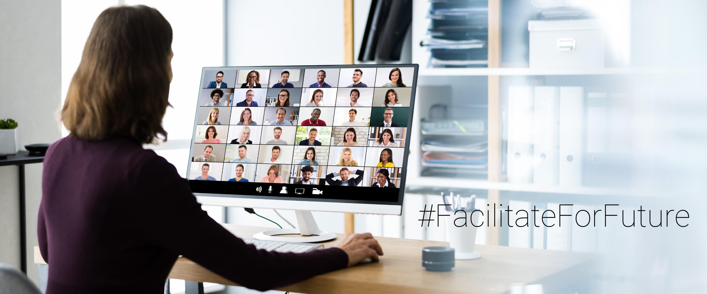 Eine Frau sitzt vor einem Bildschirm auf dem ein virtuelles Meeting käuft. Man sieht zahlreiche Gesichter.