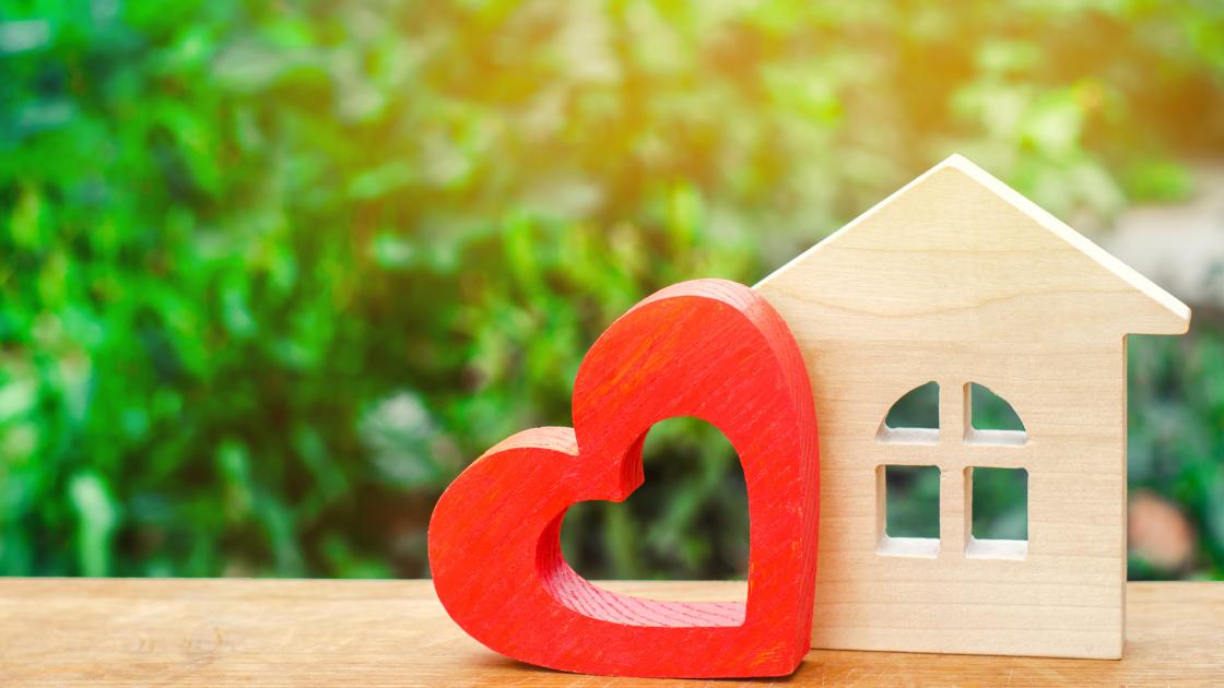 Ein Holzhaus, ein rotes Herz, im Hintergrund Grünpflanzen